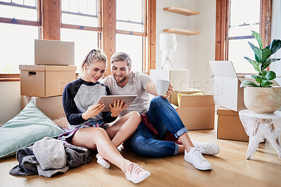 Buy stock photo Shot of a happy young couple using a tablet in their new home