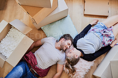 Buy stock photo High angle shot of a happy young couple being affectionate in their new home