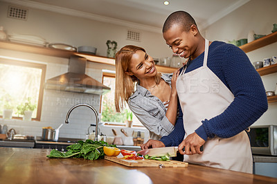 Buy stock photo Shot of a young man preparing a meal for him and his girlfriend
