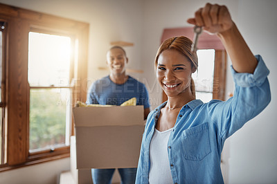 Buy stock photo Shot of a woman up the key to their new home with her boyfriend in the background