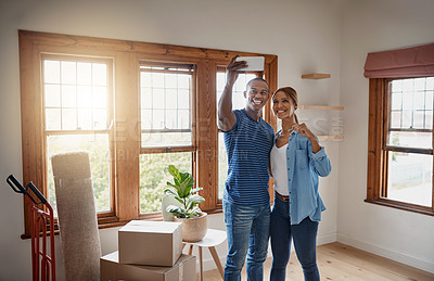 Buy stock photo Shot of a young couple taking a selfie in their new house