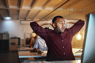 Buy stock photo Shot of a young businessman looking exhausted while working late in an office