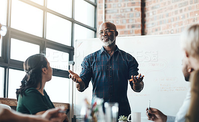 Buy stock photo Shot of a businessman giving a presentation to his colleagues in a boardroom