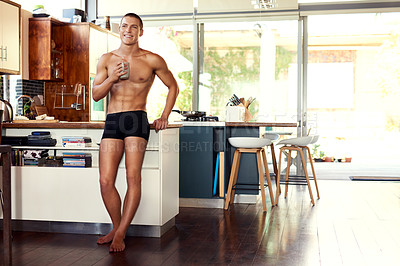 Buy stock photo Shot of a handsome young shirtless man drinking a cup of coffee in the kitchen at home