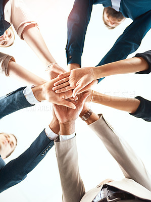 Buy stock photo Low angle shot of a group of unrecognizable business colleagues standing with their hands in a huddle in their office