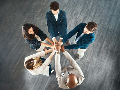 Buy stock photo High angle shot of a group of business colleagues standing with their hands in a huddle in their office