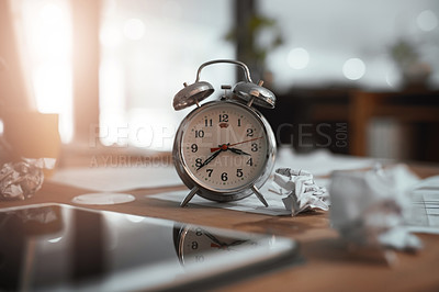 Buy stock photo Still life shot of a clock and crumpled paper on a desk in an office at night