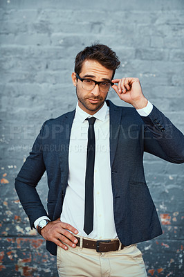 Buy stock photo Cropped portrait of a handsome young businessman standing with his hand on his hip against a grey facebrick wall