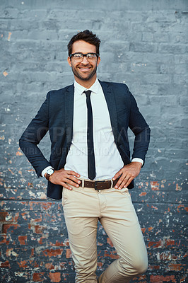 Buy stock photo Cropped portrait of a handsome young businessman standing with his hands on his hips against a grey facebrick wall