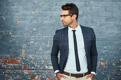 Buy stock photo Cropped shot of a handsome young businessman standing with his hands in his pockets against a grey facebrick wall