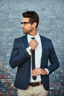 Buy stock photo Cropped shot of a handsome young businessman adjusting his tie while standing against a grey facebrick wall