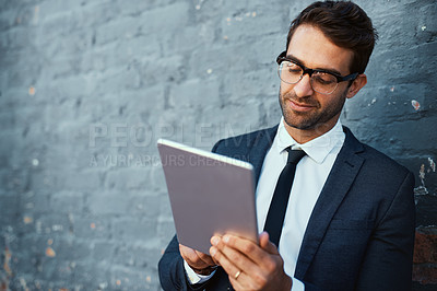 Buy stock photo Cropped shot of a handsome young businessman using his tablet while standing against a grey facebrick wall