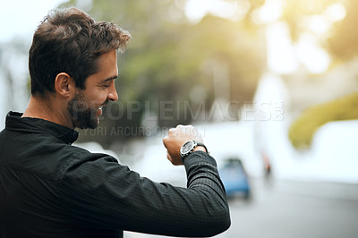 Buy stock photo Cropped shot of a handsome young man checking the time while traveling through the city