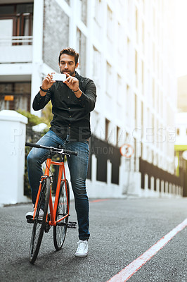 Buy stock photo Full length shot of a handsome young man taking photographs while traveling through the city by bike