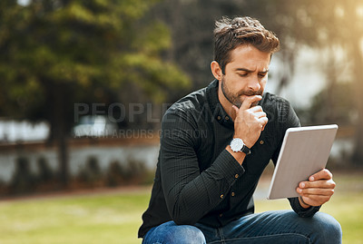 Buy stock photo Cropped shot of a handsome young man using his tablet while sitting in the park