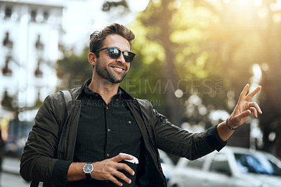 Buy stock photo Cropped shot of a handsome young man hailing a cab in the city