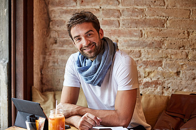 Buy stock photo Portrait of a handsome young man using his digital tablet while sitting in a cafe