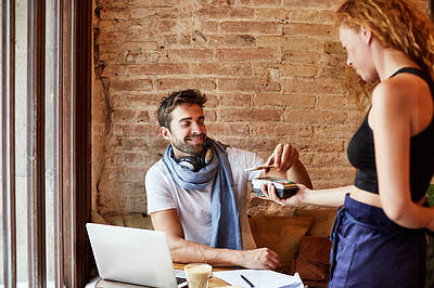 Buy stock photo Shot of a handsome young man using NFC technology to pay his waitress in a cafe