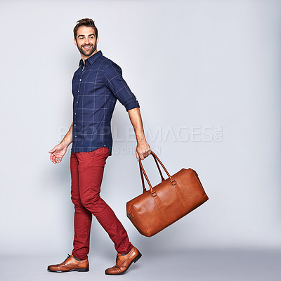 Buy stock photo Studio shot of a handsome young man carrying a suitcase against a grey background