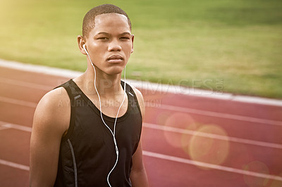 Buy stock photo Portrait of an athletic young man listening to music while standing on the track