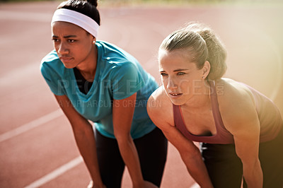Buy stock photo Shot of two young athletic women looking tired after a run on the track