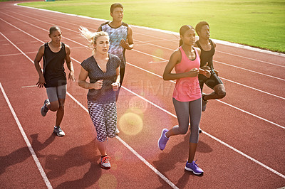 Buy stock photo High angle shot of a group of young athletes running on the track