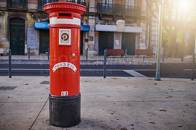 Buy stock photo Shot of a red mailbox standing on its own in the city outside during the day