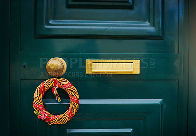 Buy stock photo Closeup of a green door with a Christmas decoration hanging on the handle outside during the day