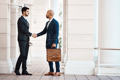 Buy stock photo Shot of young handsome businessmen shaking hands outside