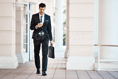 Buy stock photo Shot of a young handsome businessman on a call outside
