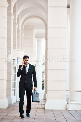 Buy stock photo Shot of a young handsome businessman on call outside