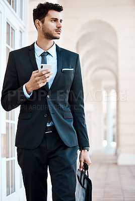 Buy stock photo Cropped shot of a handsome businessman using a cellphone outside