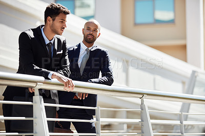 Buy stock photo Cropped shot of young handsome businessmen talking on a bridge outside