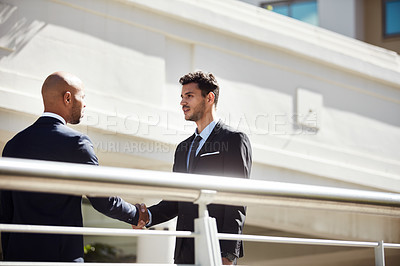 Buy stock photo Cropped shot of young handsome businessmen shaking hands on a bridge outside