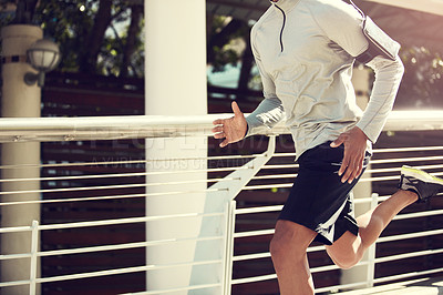 Buy stock photo Cropped shot of an unrecognizable man running on a bridge in the city