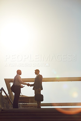 Buy stock photo Shot of handsome businessmen shaking hands on top of a staircase outside
