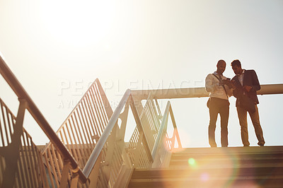 Buy stock photo Low angle shot of handsome businessmen using a cellphone on top of a staircase outside