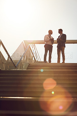 Buy stock photo Low angle shot of two businessmen using a cellphone on top of a staircase outside