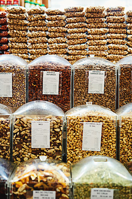 Buy stock photo Shot of a whole bunch of containers and packets full of nuts that are being displayed at a market