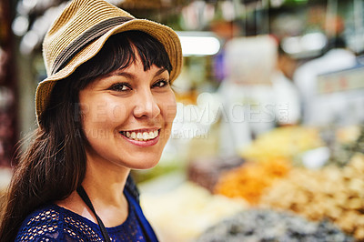 Buy stock photo Portrait of a cheerful young woman standing in the middle of a busy market outside during the day