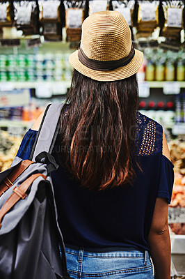 Buy stock photo Rearview shot of an unrecognizable woman browsing through a market deciding what to buy outside during the day