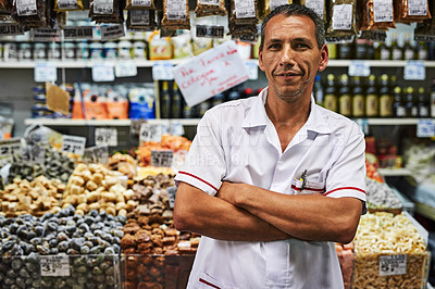 Buy stock photo Portrait of a confident middle aged man standing with his arms folded at his market stall outside during the day