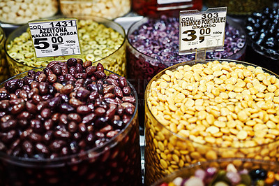 Buy stock photo Shot of numerous amounts of red olives and nuts in containers being displayed at a market during the day