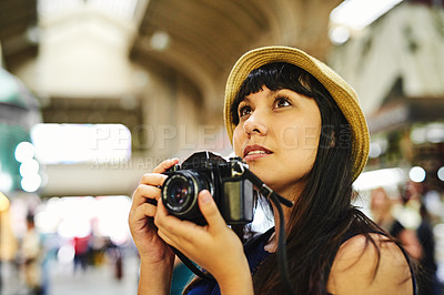 Buy stock photo Shot of a carefree young woman taking photos of a food market during the day