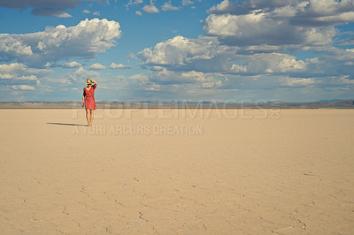 Buy stock photo Shot of a young woman walking barefoot in the desert