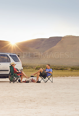 Buy stock photo Shot of a young couple camping on a desert road trip
