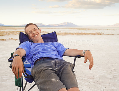 Buy stock photo Shot of a young man relaxing on a chair while out camping in the desert