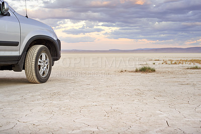 Buy stock photo Shot of a vehicle parked along the sands of an empty desert