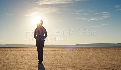 Buy stock photo Shot of a young woman walking alone in the desert