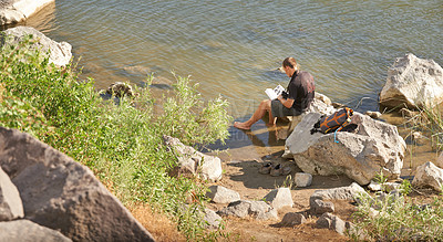 Buy stock photo Shot of a young man sitting on a rock by the river and reading a book